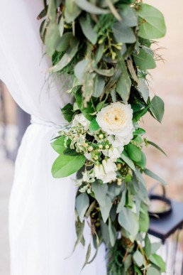 white linens and garlands of greenery